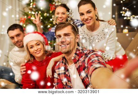 celebration and holidays concept - happy friends with glasses celebrating christmas at home party and taking selfie over snow