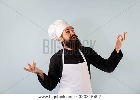 Food Concept. Bearded Chef In Uniform, Hat And Apron. Professional Chef, Cook Or Baker. Chief Cook A