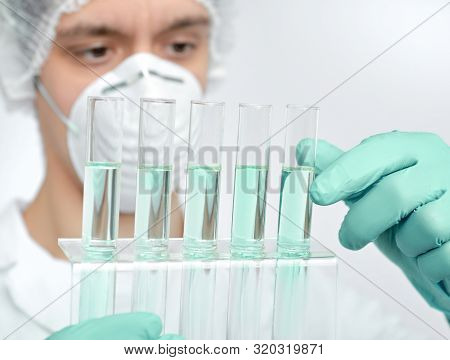 Keen Adult Male Scientist In White Gown And Protective Gloves Holding Glass Tubes With Chemical Reac