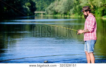 Man at riverside enjoy idyllic landscape while fishing. Fishing cause negative physiological effects for fish populations. Environmental impact of fishing includes issues such as availability of fish poster