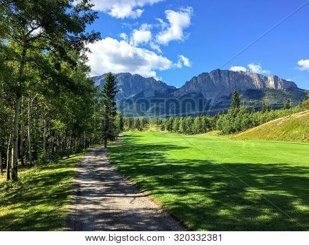 A View From The Tee Box Looking Down A Tough Par 4 Lines With Trees And The Rocky Mountains In The B