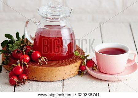 Cup of rose hip tea and fresh rose hips beside it
