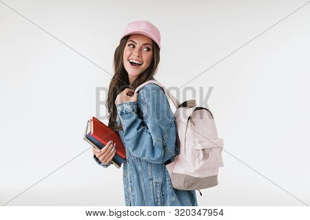 Image of a cheerful positive young emotional school girl student with backpack and books isolated over white wall background.