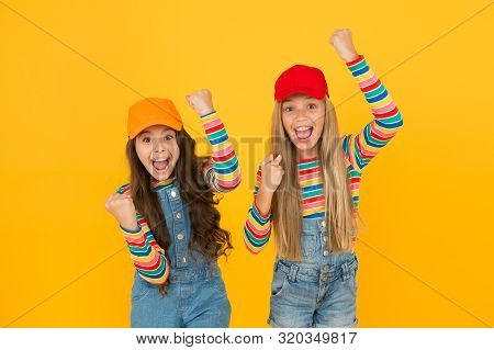 Being Happy And Victorious. Little Girls Making Victory Gestures On Yellow Background. Cute Small Wi