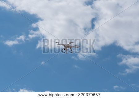 Quadcopter, multirotor, multicopter, drone, copter, unmanned aircraft system flying the blue sky. Modern video and aerial photography poster