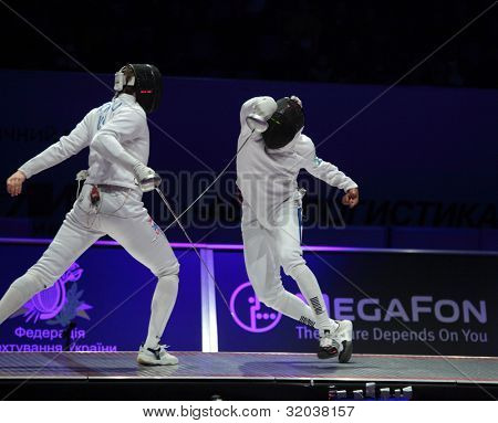 KIEV, UKRAINE - APRIL 14, 2012: Fight between Soren Thompson, USA, and Ulrich Robeiri, France, during final match of World Fencing Championship on April 14, 2012 in Kiev, Ukraine