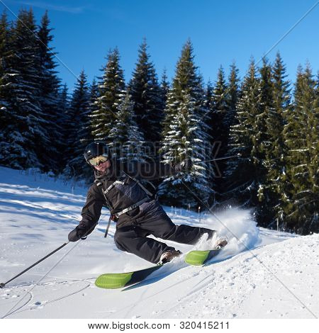 Front View Of Proficient Skier In Black Skiing Carving On Low Snow-covered Hill. Training And Vacati