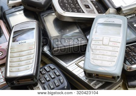 Bunch Of Old Used Outdated Mobile Phones. Recycling Electronics In The Market Cheap