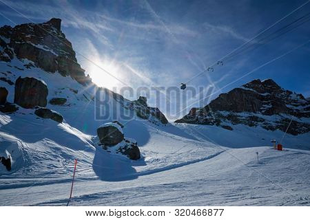 View of a ski resort piste with people skiing in Dolomites in Italy with cable car ski lift. Ski area Arabba. Arabba, Italy
