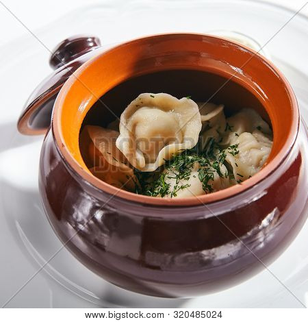 Traditional Russian dumplings in a clay ceramic pot with finely chopped dill and sour cream isolated. Macro shot of dumplings, jiaozi, dimsum or momo stuffed with meat, fish and vegetables closeup