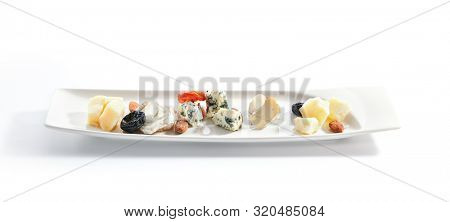 Cheese assorti platter closeup. Gorgonzola, brie, parmesan and chevre slices. Cow and goat milk chopped cheese on plate. Served delicious snacks composition isolated on white background