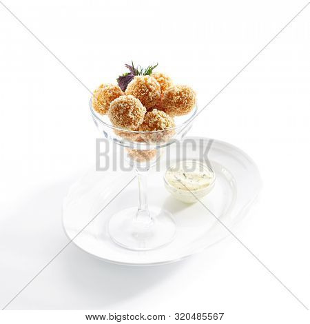 Macro shot of breaded cheese balls with mozzarella, cottage cheese and Tartar sauce in transparent bowl isolated on white background. Traditional Italian stuffed rice cheese balls arancini closeup