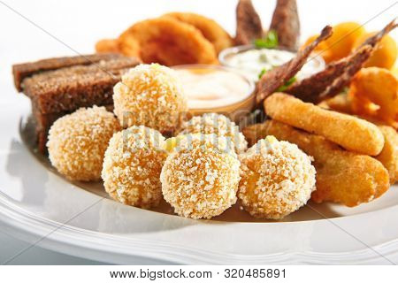 Macro shot of deep-fried snack plate with crisp potato croquettes or potatoes balls on blurred background. Traditional Italian arancini cheese balls on white restaurant plate closeup