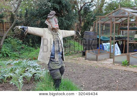 Scarecrow in English garden with arms outstretched