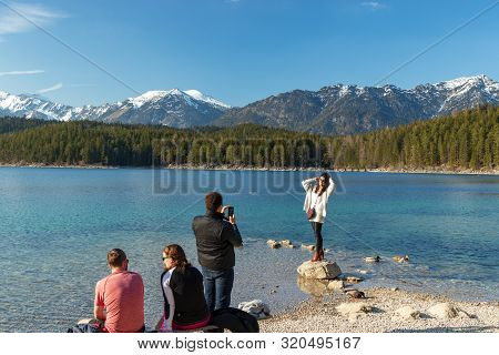 Eibsee, Germany, March 31, 2019: Husband Taking Selfie Of His Wife For Instagram At Eibsee