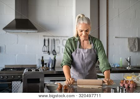 Happy senior woman preparing christmas cookies at home. Mature woman rolling dough for biscuits on kitchen counter. Old lady wearing apron rolling pastry with wooden rolling pin and smiling.