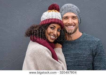 Young multiethnic couple in warm clothing looking at camera on a winter day isolated on gray wall with copy space. Portrait of smiling man and beautiful happy woman hugging against grey background.