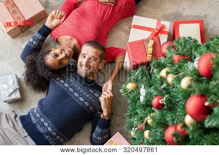 High angle view of young man and african woman lying on floor near christmas tree with presents. Top view of happy multiethnic couple lying down near xmas gifts holding hands and looking at camera.