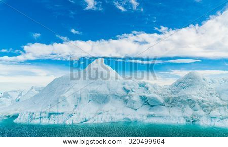 Global warming - Greenland Iceberg landscape of Ilulissat icefjord with giant icebergs. Icebergs from melting glacier. Arctic nature heavily affected by climate change