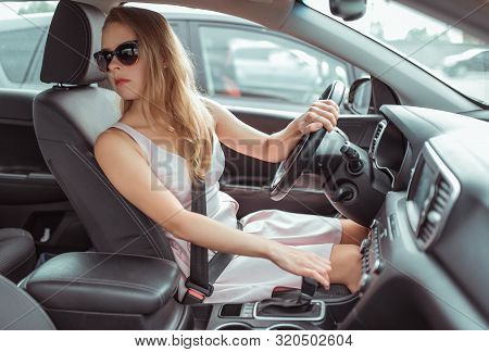 A Woman In A Car Rides In Reverse, Parks Car In Parking Lot, Sits Behind The Wheel, In City In Summe