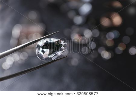Tweezers With Jewel Over Table. Space For Text