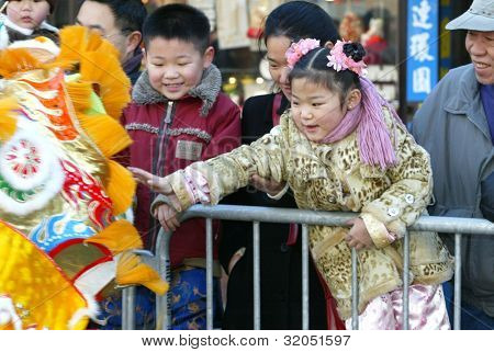 FLUSHING, NY - FEB 12: A young parade goer touches a dragon dancer as they attend a Chinese New Year Parade on February 12, 2005 in the Flushing neighborhood of New York City.