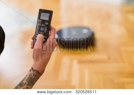 poster of Close up of man hands controling automatic vacuum cleaner using electronic control of the mopping robot
