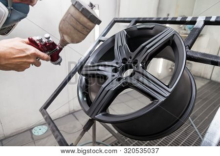 Painting the element body of the car - the aluminum alloy wheel with the help of aerograf in black color by the hand of painter repairman in the industrial professional garage. Auto service industry. poster