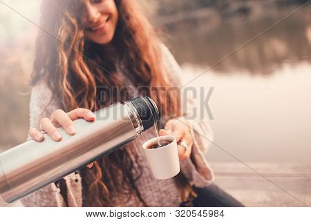 Happy Woman In Cozy Knitted Sweater Pouring Tea From Thermos In Cup. She Is Sitting Near Lake In Aut
