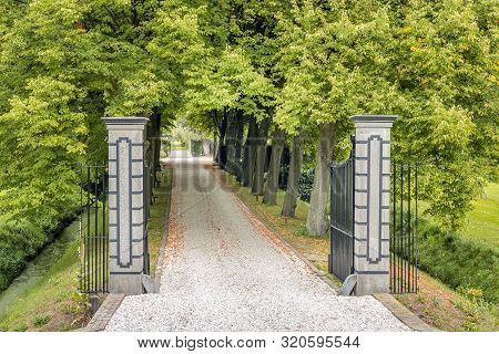 Opened Black Wrought Iron Gate Between Stone Pillars. Behind The Fence Is A Driveway Covered With Li