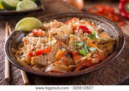 A Bowl Of Delicious Chicken Pad Thai With Rice Noodles, Red Bell Pepper, Peanut, Carrot, Ciliantro A