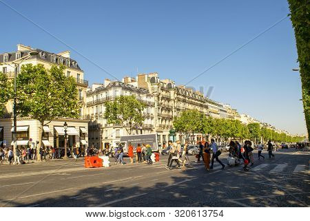 Paris / France - July 4, 2019: People On Pedestrian Crossing In The Famous French Boulevard Champs E