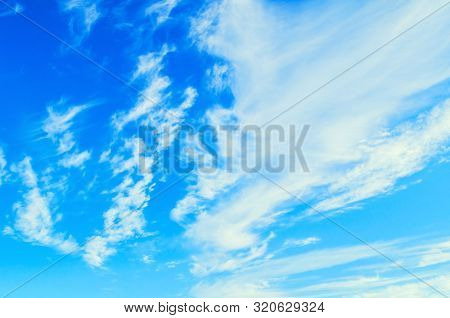 Dramatic blue sky background. Picturesque colorful clouds lit by sunlight. Vast sky landscape panoramic scene - colorful sky view in bright tones. Blue sky landscape, vast sky view with white sky clouds