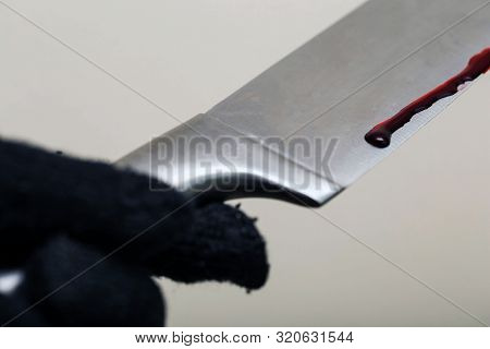 Murder And Crime Scene Concept - Close Up Of Criminal Or Murderer Hand In Glove With Blood On Knife