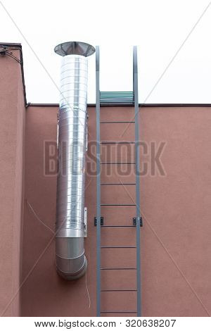 Tin Pipe On Building Wall And Stairs To Roof