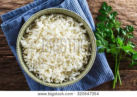 Freshly Grated Raw Cauliflower Rice In Bowl With Fresh Parsley Leaves On The Side, Photographed Over