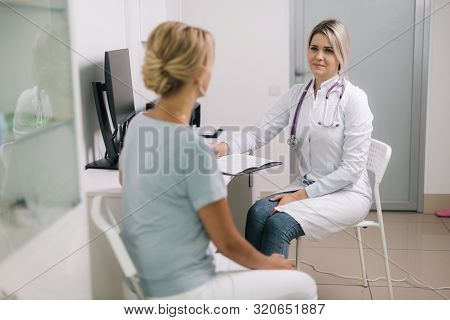 Doctor Consulting Young Woman In Hospital. Serious Female Therapist Consulting And Diagnose Woman. M