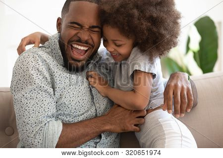 Excited African American Dad Tickling Little Daughter.