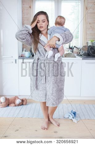 Young beautiful tired sterssed exhausted mother with baby girl child. Postnatal depression, motherhood difficulty idea concept.