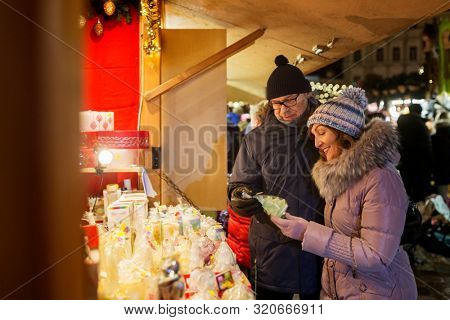 shopping, winter holidays and people concept - happy senior couple at christmas market souvenir shop stall on town hall square in tallinn, estonia