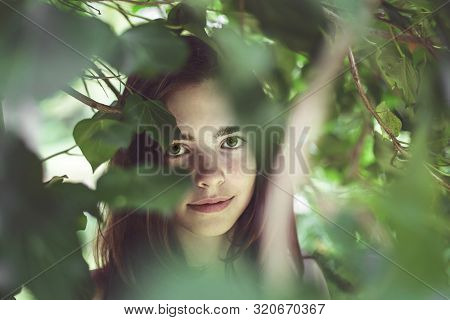 Portrait Of A Young Smiling Woman Covered Of Blurred Leaves