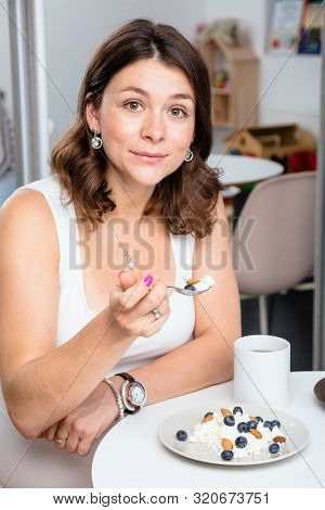 Portrait of young pregnant woman wearing white shirt eating cottage cheese with berries and nuts in a cafe - healthy nutrition and pregnancy concept