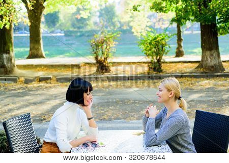Female Friends Sit In Coffee Shop And Enjoy Talk. Friendship Meeting. Togetherness And Female Friend