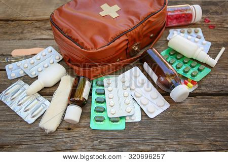 First Aid Kit On Old Wooden Background.
