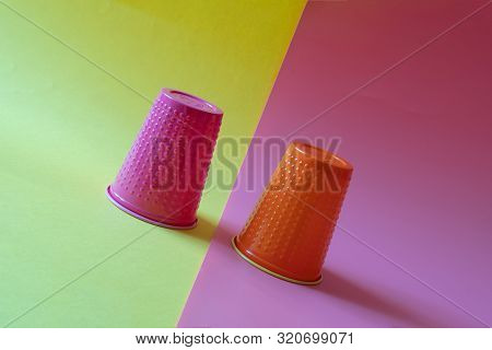 Two multi-colored plastic cups tilted on a yellow and pink background. Concept of business volatility and falling investment poster