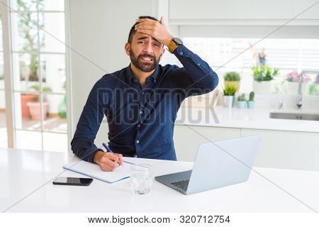 Handsome hispanic man working using computer and writing on a paper stressed with hand on head, shocked with shame and surprise face, angry and frustrated. Fear and upset for mistake.