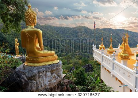 Golden Buddha statue of the Wat Phra That In Kwaen temple at sunset with view point, Phrae province, Thailand