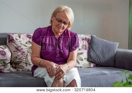Old Age, Health Problem And People Concept - Senior Woman Suffering From Pain In Leg At Home. Senior