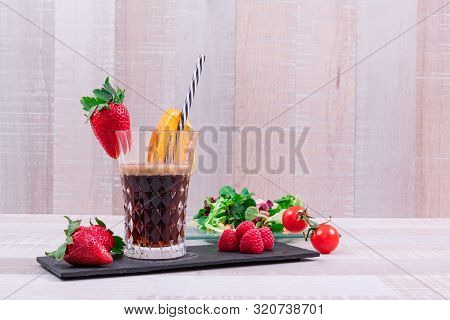Fresh red strawberries served with a glass of coca and a slice of ripe orange served with a nutritious tropical salad on the back, with a wooden base. Healthy food concept. poster