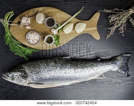 Board With Fresh Raw Salmon On Wooden Table, With Salt, Pepper, Garlic, Lemon, Dill, Parsley, Dry Th